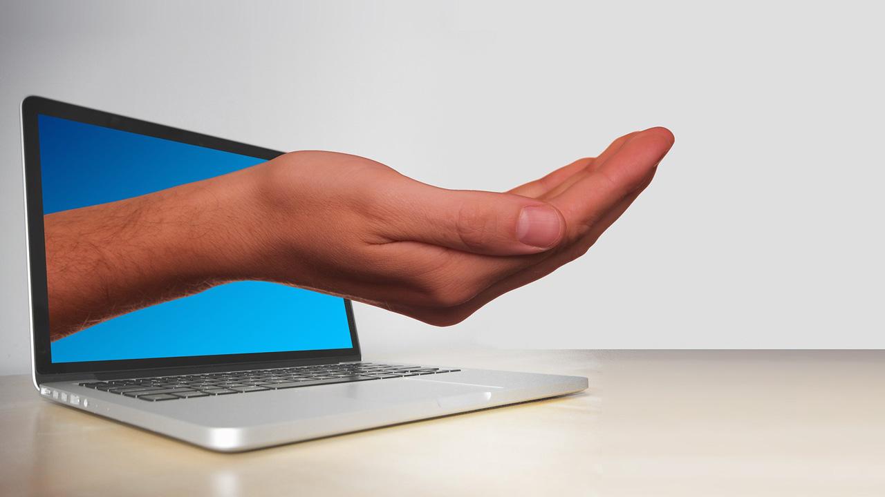 Hand ragt aus dem Monitor